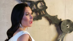 Beautiful young woman sing near dial of big clock in studio Stock Footage