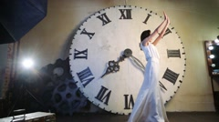 Beautiful young woman posing against dial of big clock in studio Stock Footage