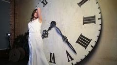 Young singer sing and posing against dial of big clock in studio Stock Footage