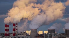 Smoke pollution from power plant smokestacks over urban cityscape at sunset. Stock Footage