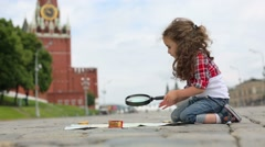 Little girl sits with map and magnifying glass on Red Square Stock Footage