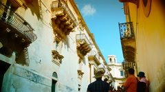Baroque ornamental statues under the balconies with tourists, in Noto,4k Stock Footage