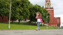 Little girl goes and closes her eyes with palms on Red Square Stock Footage