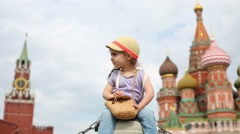 Little girl in cap sits with small bag on Red Square in Moscow Stock Footage