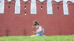 Little girl sits near walls on Moscow Kremlin and looks in bag Stock Footage