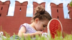 Little girl sits near big red walls on Moscow Kremlin Stock Footage
