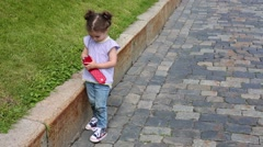 Little girl holds smartphone and walks on pavement near border Stock Footage