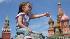 Girl sits on Red Square and points to St. Basil Cathedral Stock Footage