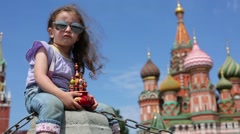 Little girl sits with toy temple near St. Basil Cathedral Stock Footage