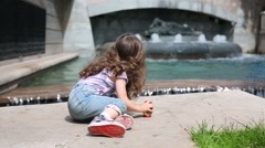 Little curly girl sits with matrioshka near fountain at summer Stock Footage