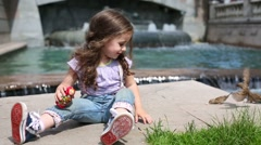 Little curly girl with matrioshka feeds sparrows near fountain Stock Footage