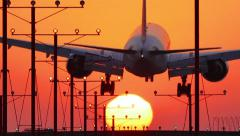 Jumbo jet plane landing in airport at sunset, flying into sun. Slow motion. Stock Footage