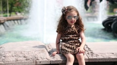 Little curly girl in sunglasses sits near fountain and shouts Stock Footage