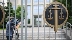 Videographer back behind iron gates of court Stock Footage