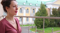 Young beautiful woman sits on balcony and watches outside Stock Footage