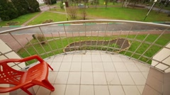 Balcony with red chair, park and yellow building at dull day Stock Footage