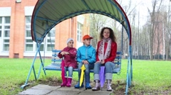 Mother and two children swing with fold colored umbrellas Stock Footage