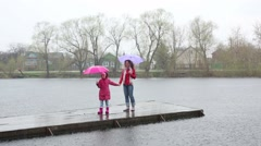Happy woman and daughter with umbrellas stand on wooden pier Stock Footage