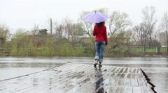 Woman with purple umbrella turns and walks on wooden pier Stock Footage