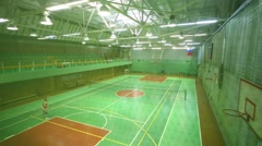 Above view of two women playing tennis in indoor athletic field Stock Footage