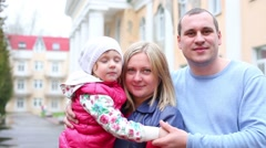 Happy mother, father and daughter hug on street at cloudy day Stock Footage