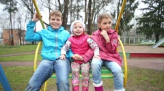 Cheerful boy and two girls in bright jackets shout on swings Stock Footage