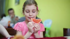 Little cute girl in pink tries slice of grapefruit in refectory Stock Footage