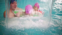 Father with two daughters swim through waterfall in pool Stock Footage