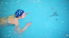 Above view of woman in cap swimming in water of pool Stock Footage