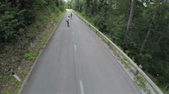 AERIAL: Longboard skaters driving down the road in slow motion Stock Footage