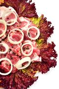 raw meet pieces with sliced onion and black pepper - stock photo