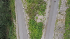 Direct fly over longboard skaters riding through serpentine Stock Footage