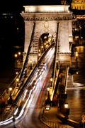 public transport on the suspension bridge at night in budapest - stock photo