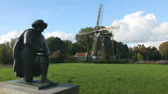 Rembrandt statue with windmill in background Stock Footage