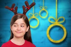 Composite image of festive little girl wearing antlers Stock Photos