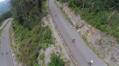 Big group of longboard riders speeding down the road aerial Stock Footage