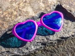 Heart-shaped pink sunglasses - stock photo