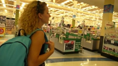 Young Woman Passing Checkout Lane of Supermarket. Stock Footage