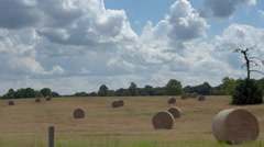 Driving by hay bales in a field Stock Footage