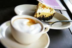 cup of frothy coffee and cake - stock photo
