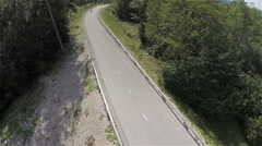 Above forest road shot with longboarders driving through Stock Footage