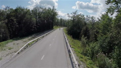 Flying over road towards forest with person on longboard speeding in front Stock Footage