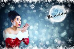 Composite image of pretty santa girl blowing over her hands Stock Illustration