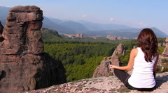 Woman doing yoga exercises on Belogradchik rocks Stock Footage