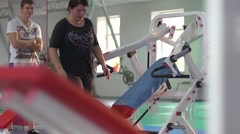 Young woman with overweight trains in the gym under the supervision of coach Stock Footage