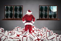 Composite image of santa standing on pile of gifts Stock Illustration