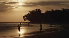 Wide shot of boys wading on beach at sunset / Esterillos, Costa Rica Stock Footage