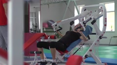 Young beautiful woman trains in the gym under the supervision of the coach Stock Footage