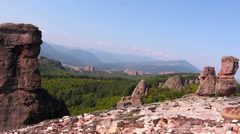 Male feet in sport shoes step on a rock, tourist admire the Belogradchik valley Stock Footage