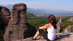 Woman sitting on a rock and admiring the beautiful Belogradchik valley Stock Footage